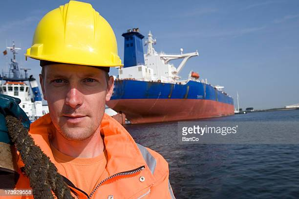 Working at the harbor between big cargo ships.