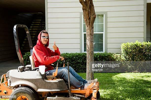 Working class.  Man mows lawn using industrial lawn mower.