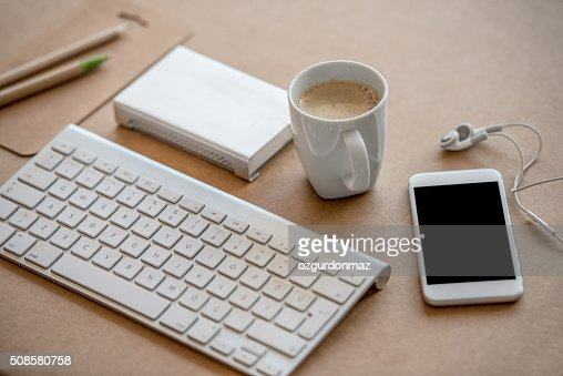 Working desk with keyboard, coffee, cell phone and hard disc : Stock Photo