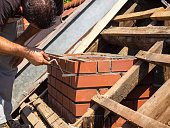 Man is measuring mortar thickness on chimney for new line of bricks on an old house in Ljubljana, Slovenia