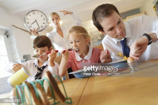 Working family at breakfast, mum pointing at clock