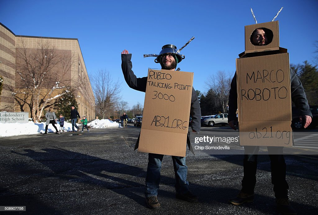 Working for the American Bridge 21st Century super PAC, Eddie Vale (L) and Kevin McAlister wear robot costumes outside a town hall event with Republican presidential candidate Sen. Marco Rubio (R-FL) at Londonderry High School February 7, 2016 in Londonderry, New Hampshire. McAlister and Vale wore the costumes so to capitalize on New Jersey Governor Chris Christie's attack on Rubio's style and delivery of talking points. Hundreds of people came to the event to see Rubio just two days before voters go to the polls in the 'First in the Nation' presidential primary.
