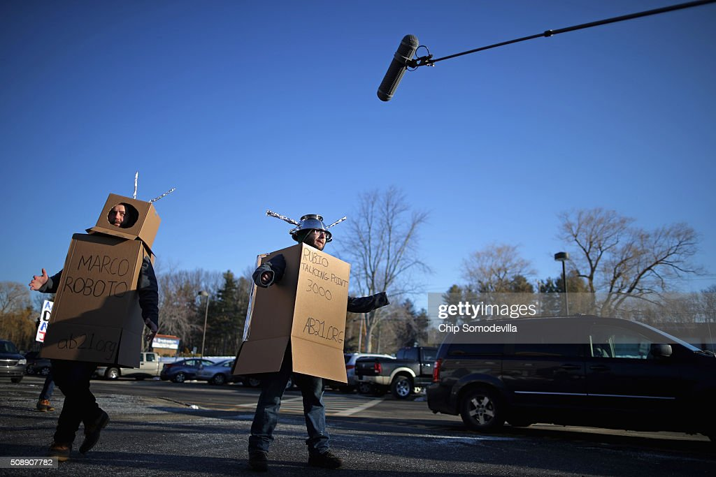 Working for the American Bridge 21st Century super PAC, Kevin McAlister (L) and Eddie Vale wear robot costumes outside a town hall event with Republican presidential candidate Sen. Marco Rubio (R-FL) at Londonderry High School February 7, 2016 in Londonderry, New Hampshire. McAlister and Vale wore the costumes so to capitalize on New Jersey Governor Chris Christie's attack on Rubio's style and delivery of talking points. Hundreds of people came to the event to see Rubio just two days before voters go to the polls in the 'First in the Nation' presidential primary.
