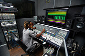 Deejay sitting in front of stereo system in studio