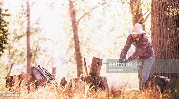 Arbeitet man teilt Holz sitzend auf Baumstumpf mit Axt