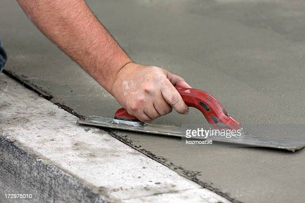 Working man troweling concrete