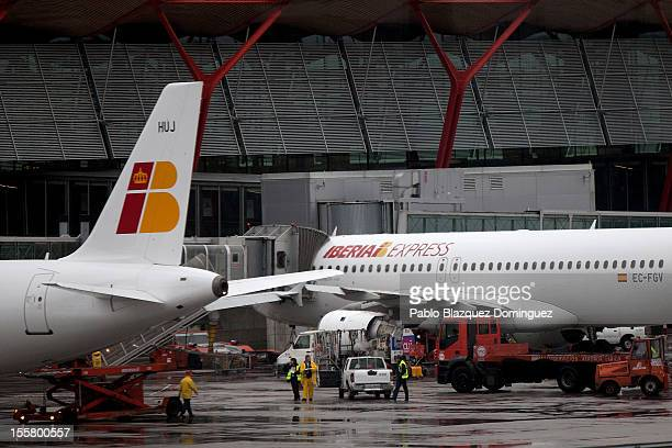 Working men stand in the parking area of Iberia's planes at Barajas Airport on November 8 2012 in Madrid Spain Spanish airline Iberia which partnered...