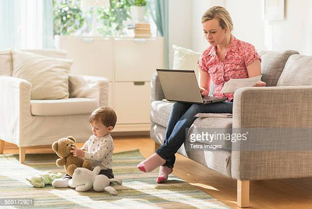 Working mother and son (2-3 years) in living room
