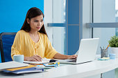 Pretty Filipina young woman working on laptop in office