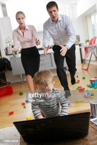 working parents rushing to stop child on laptop : Stock Photo
