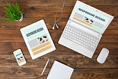 Working Place of web Designer on wood Table with responsive Site Theme on Laptop Tablet and Telephone Screens and blank Page of Paper Notepad Top View flat Lay