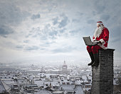 old man dressed as santa claus sitting on top of a chimney writing on his computer
