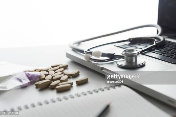 working space of Doctor with stethoscope with medicine tablet and notebook for consult patient