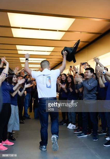Working staff cheer for the first one who buy the newly released iPhone X at the Sanlitun Apple Store on November 3 2017 in Beijing China iPhone X go...