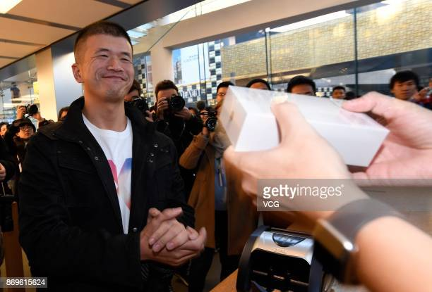 A working staff member passes the newly released iPhone X to an Apple fan at the Sanlitun Apple Store on November 3 2017 in Beijing China iPhone X go...