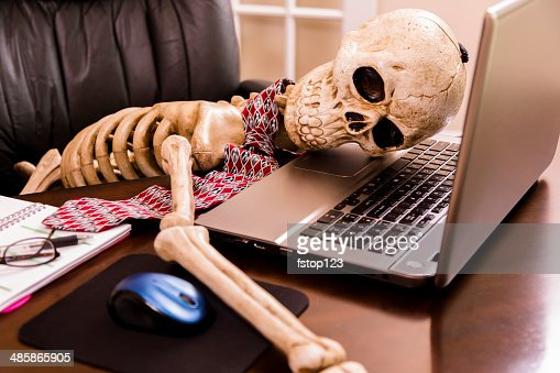 Working to death.  Business man's skeleton using laptop in office.