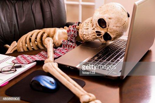 Lavorare al decesso.  Scheletro di un uomo d'affari utilizzando il computer portatile in ufficio.