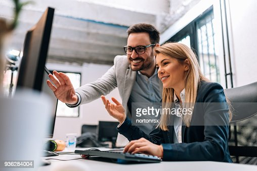 Working together on project. Two young business colleagues working on computer : Stock Photo