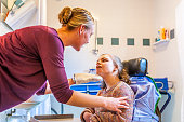A disabled child in a wheelchair being cared for by a nurse in the bathroom.