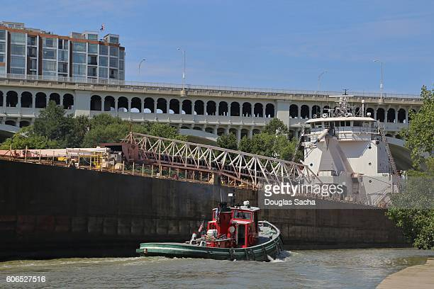 Working Tugboat assisting a Cargo ship through a narrow river, Cleveland, Ohio, USA
