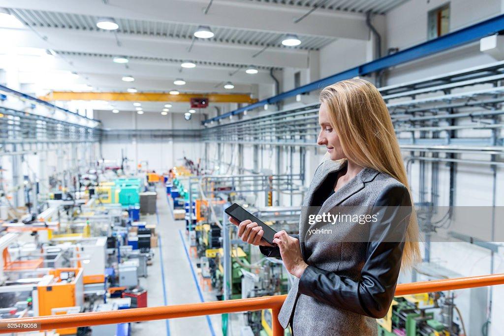Travaillant avec une tablette dans le quartier futuriste de usine : Photo