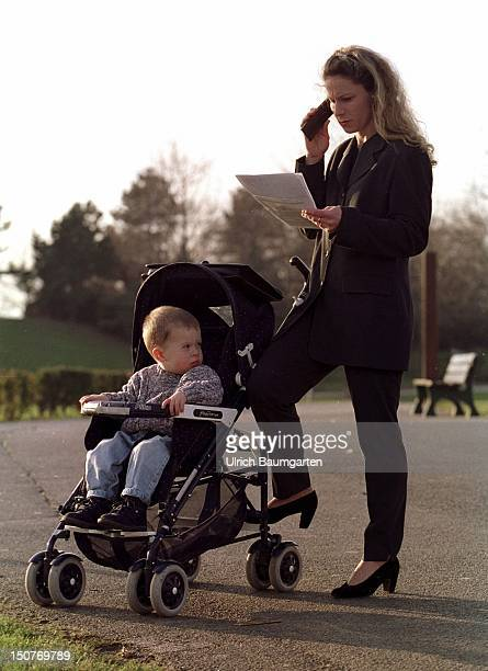 Working young mother calling from her handy whilst taking a walk