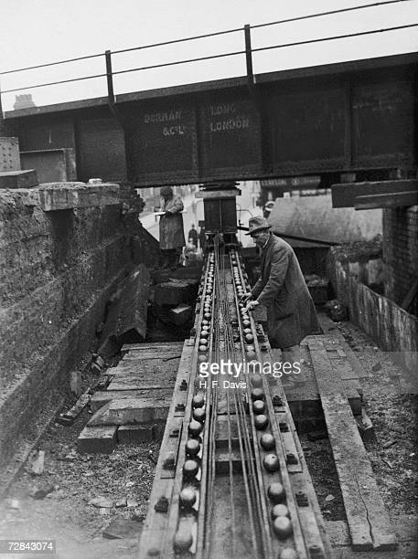 A workman adjusting a slide system of steel balls along which a 215ton steel railway bridge will be moved into position 14th January 1934 The bridge...