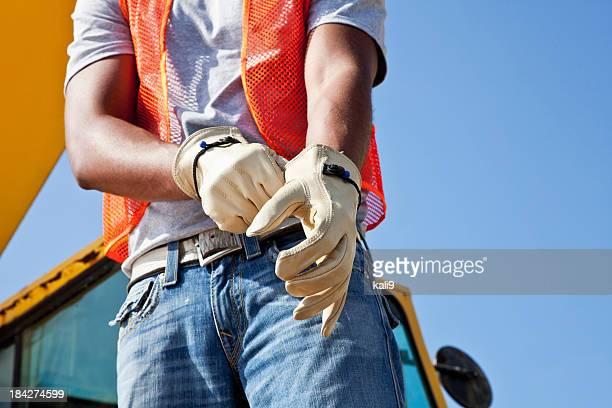 Workman auf Baustelle setzen auf Handschuhe
