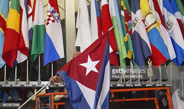 A workman at the US Department of State add the Cuban flag at to the display of flags inside the main entrance at 202 'C' Street at 4am local time in...