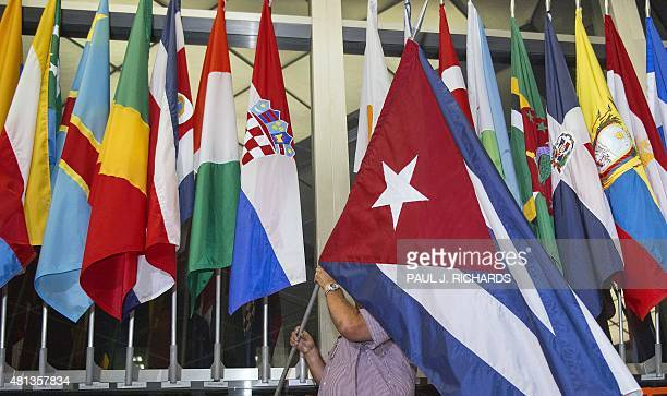 A workman at the US Department of State adds the Cuban flag between Croatia and Cyprus ones at to the display of flags inside the main entrance at...