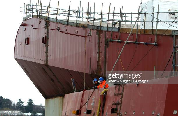 Workman at work near the take off ramp on the deck of HMS Queen Elizabeth Aircraft Carrier at Rosyth Docks