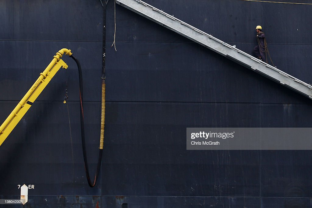 A workman boards a container ship as it is unloaded in the Port of Singapore on February 1, 2012 in Singapore. The Port of Singapore is the world's businest port in terms of total shipping tonnage moving through it, and second only to Shanghai in terms of total cargo tonnage moved. The port is an essential part of Singapore's economy, responsible not only for incoming and outgoing freight, but also for processing of natural resources such as crude oil refinement. It connects to 600 other ports in 123 countries.