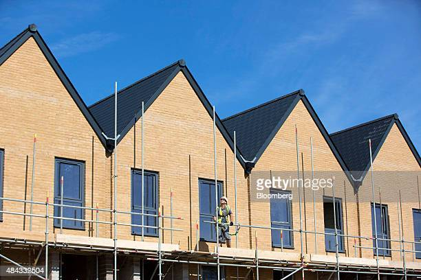A workman breaks down scaffolding on a building exterior at a Persimmon Plc construction site in Uxbridge UK on Monday Aug 17 2015 Persimmon Plc the...