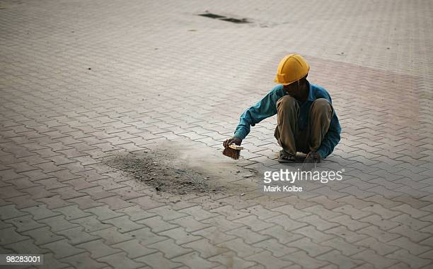 A workman brushes the pavement in the town market on April 1 2010 in Chandigarh India