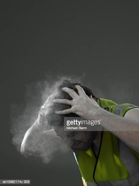 Workman brushing white powder out of hair