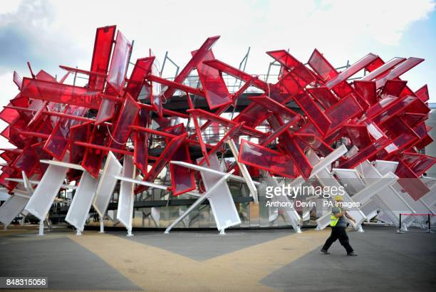 A workman carries a brush past the newly completed CocaCola Beatbox building in the Olympic park Stratford London