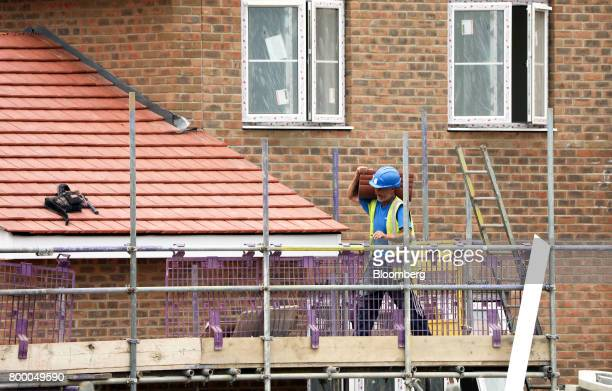 A workman carries a stack of roof tiles on a housing development under construction in Maldon UK on Thursday June 22 2017 UK house prices recorded...
