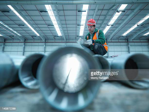Workman checking pipes on building site in partly completed factory