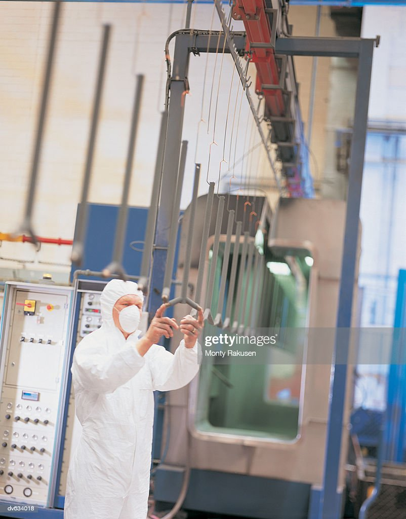 Workman checking products before powder coating : Stock Photo