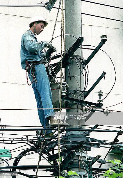 A workman checks the power cables along a street in Shanghai 31 December 1999 ahead of the new year Chinese authorities are making last minute checks...