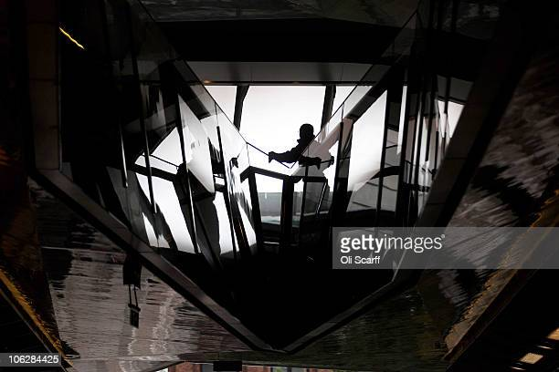 A workman cleans a banister prior to the official opening of the newly completed shopping centre 'One New Change' on October 28 2010 in London...
