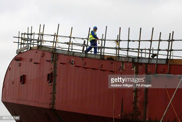 A workman crosses the take off ramp on the deck as work continues on HMS Queen Elizabeth Aircraft Carrier at Rosyth Docks