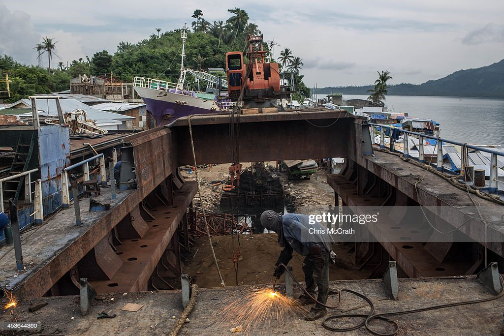 A workman cuts through the deck of a large ship that is being broken down for scrap after it was pushed ashore by Typhoon Yolanda in the township renamed by residents as ' Yolanda Village' on August 15, 2014 in Tacloban, Leyte, Philippines. Residents of Tacloban city and the surrounding areas continue to focus on rebuilding their lives nine months after Typhoon Haiyan struck the coast on November 8, 2013, leaving more than 6000 dead and many more homeless. With many businesses and government operations back up and running and with the recent start of the years typhoon season, permanent housing continues to be the main focus with many families still living in temporary accommodation. As well as continuing recovery efforts Leyte is preparing for the arrival of Pope Francis, who will visit the region from January 15- 19.
