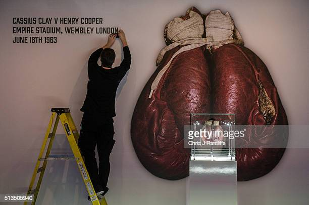 A workman fixes lettering on to the wall by the Ali 'split glove' from the 1963 fight v Henry Cooper at Wembley when Ali's glove split in the forth...