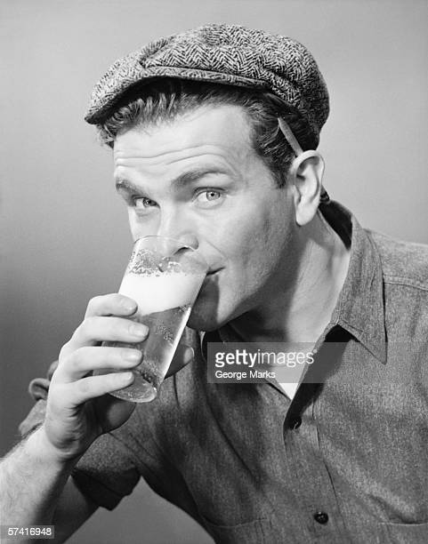 Workman in cap drinking beer in studio, (B&W), (Close-up), (Portrait)
