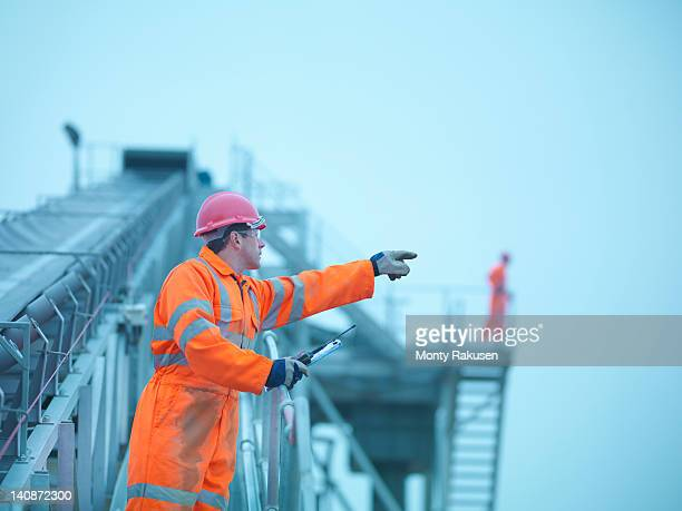 Workman in reflective clothing pointing from steps of screening conveyor at quarry