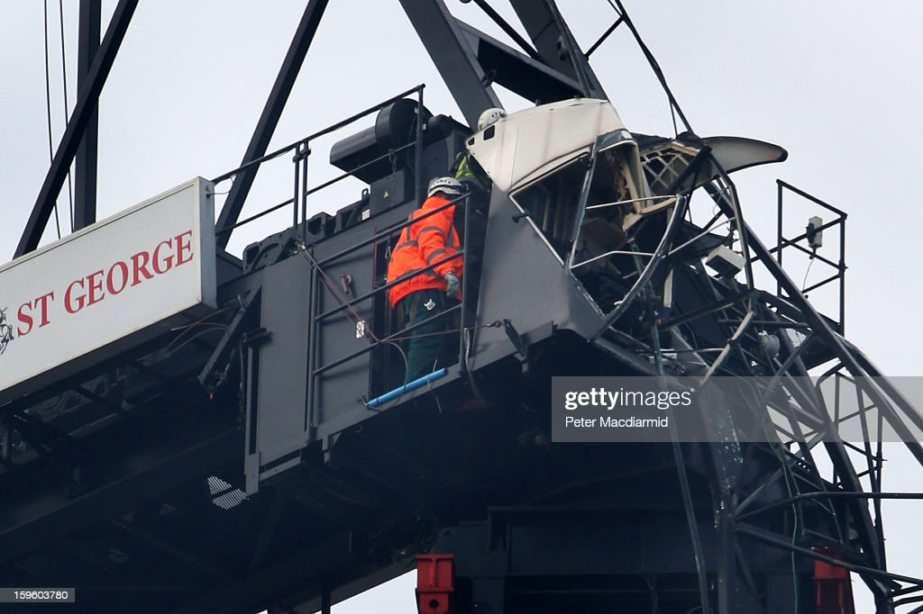 A workman inspects damage to a crane and the exposed drivers cab on the St George's Wharf building after a helicopter crashed into it on January 17, 2013 in London, England. Police cordons have remained in place as investigations continue into the cause of yesterday's helicopter crash in which two people died.