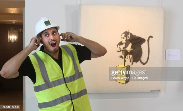 A workman jokes near Banksy's Monkey Detonator that is expected to fetch 70000 90000 during a photocall for highlights from Bonhams' Urban Art Sale...