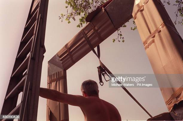 A workman oversees the placing of a large metal frame onto the Evening Standard show garden during the build up to the Chelsea Flower Show 2000 The...