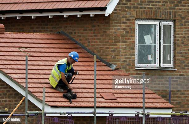 A workman prepares to fix tiles to a roof on a housing development under construction in Maldon UK on Thursday June 22 2017 UK house prices recorded...